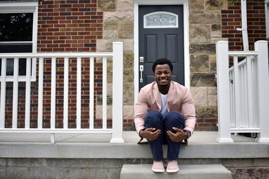 New homeowner Emerald Huggins proudly sits in front of his home