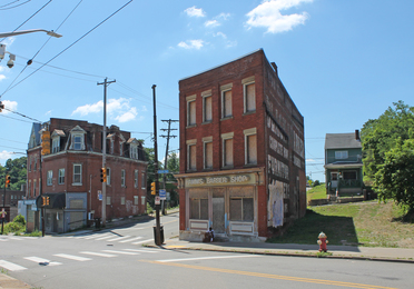 The former Hamm's Barber Shop building stands three-stories tall and boarded up on Centre Avenue in the Hill District.